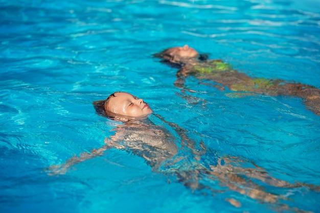 Gelukkige jonge geitjes spelen in het blauwe water van het zwembad.
