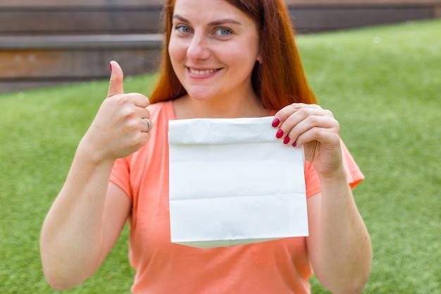 Gelukkige jonge gembervrouw toont hand met duimen omhoog en houdt pakket met voedsel vast. ruimte kopiëren. mockup van blanco pakket