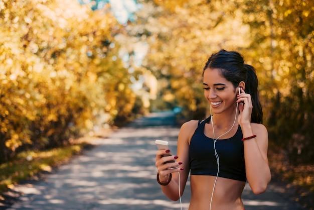 Gelukkige jonge geschikte vrouw die celtelefoon met behulp van terwijl het luisteren aan muziek op smartphone in park.