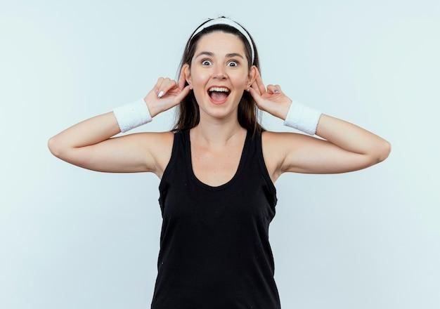 Gelukkige jonge geschiktheidsvrouw die in hoofdband camera bekijkt die haar oren glimlachend vrolijk status over witte achtergrond toont
