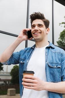 Gelukkige jonge geweldige man zakenman poseren buiten buiten wandelen praten door mobiele telefoon koffie drinken.