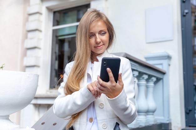 Gelukkige jonge glimlachende vrouw die een smartphone openlucht op de uitstekende stijlladder gebruiken