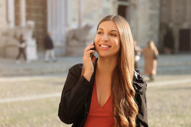 Gelukkige jonge glimlachende vrouw die op mobiele telefoon op europese stadsstraat spreekt.