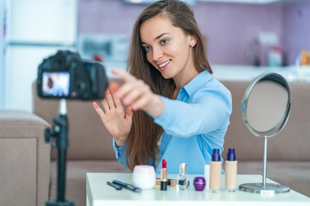 Gelukkige jonge glimlachende vrouw video blogger tijdens het opnemen van haar schoonheid vlog over make-up en cosmetica thuis. bloggen en live streamen