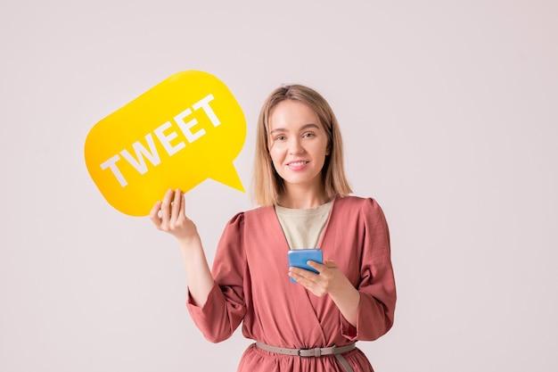 Gelukkige jonge glimlachende vrouwelijke duizendjarige met geel papier tekstballon posten in haar profiel terwijl ze online communiceert