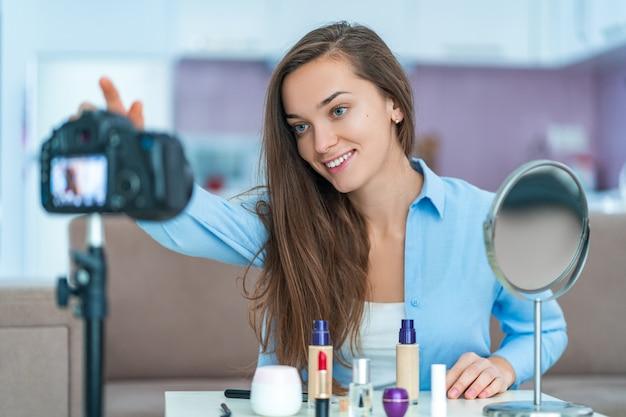 Gelukkige jonge glimlachende vrouwen videoblogger tijdens het opnemen van haar schoonheidsblog en vlog over make-up en schoonheidsmiddelen thuis. bloggen en live streamen