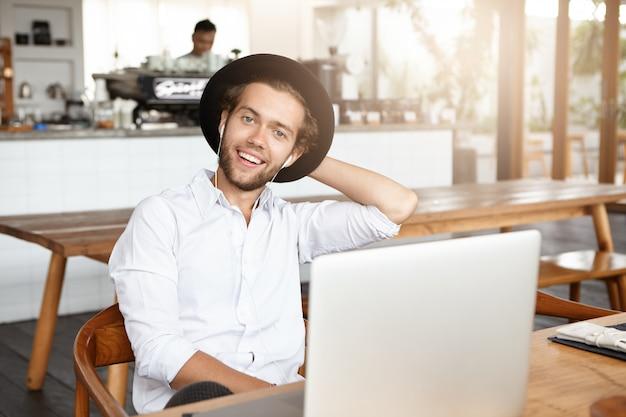 Gelukkige jonge hipster die wit overhemd en modieuze hoed draagt die vrolijke gezichtsuitdrukking heeft