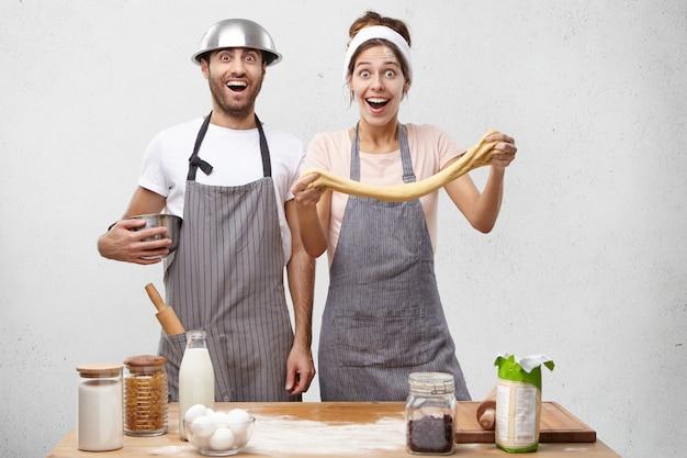 Gelukkige jonge huisvrouw strekt het deeg in handen, maakt het voor het bakken van theecake, krijgt hulp van echtgenoot