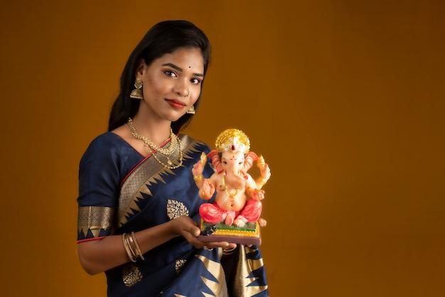 Gelukkige jonge indiase vrouw poseren met ganesha standbeeld ter gelegenheid van ganesh festival