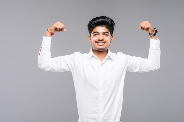 Gelukkige jonge indische mens die bicepsen over grijze muur toont