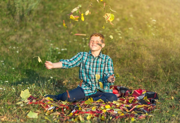 Gelukkige jonge jongen die de herfstbladeren in de lucht werpt