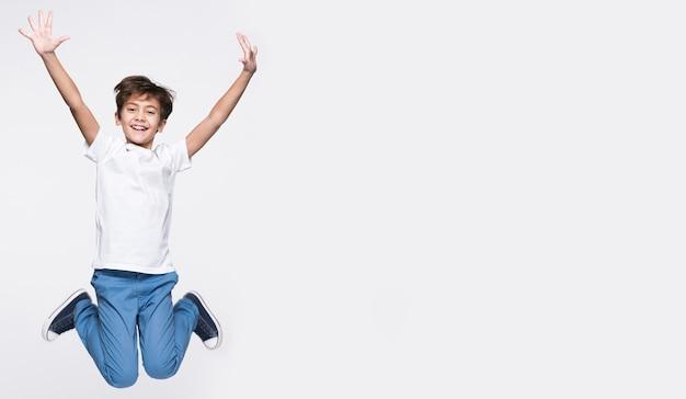 Gelukkige jonge jongen die met exemplaar-ruimte springt
