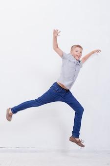 Gelukkige jonge jongen die op witte achtergrond springt