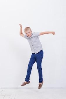Gelukkige jonge jongen die op witte muur springt
