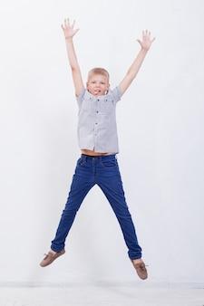 Gelukkige jonge jongen die over een witte achtergrond springt