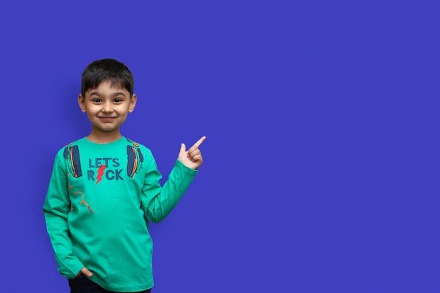 Gelukkige jonge jongen in shirt die omhoog wijst en arm wit vasthoudt, kijkend naar de camera over geïsoleerde achtergrond en kopieer ruimte