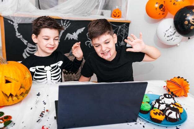 Gelukkige jonge jongens, broers praten met grootouders via videogesprek met laptop op halloween-dag, opgewonden jongens in kostuums kijken computer zwaaien en glimlachen.