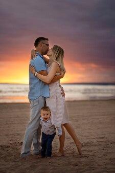 Gelukkige jonge kaukasische mooie familiezonsondergang op het strand in de zomer mooie hemel op achtergrond
