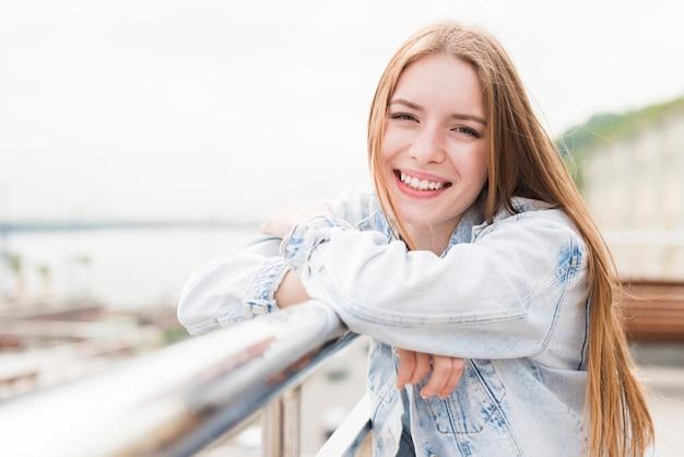 Gelukkige jonge kaukasische vrouw die camera met gekruist wapen bekijkt
