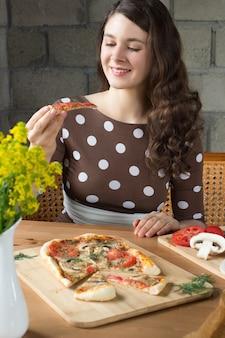 Gelukkige jonge kaukasische vrouw die een pizza met paddestoelen in een koffie eet of thuis.