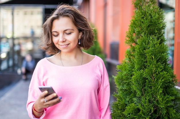 Gelukkige jonge kaukasische vrouw die interessant plaatsen in smartphone doorbladeren.