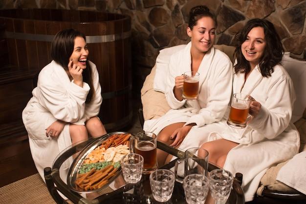 Gelukkige jonge kaukasische vrouwen in badjas zitten naast het zwembad in de sauna, koud bier drinken.