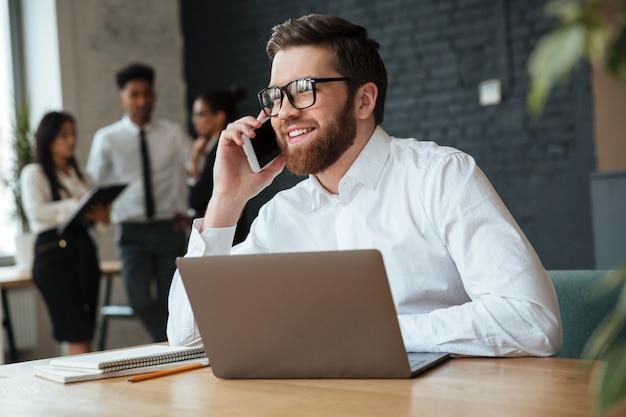 Gelukkige jonge kaukasische zakenman die door mobiele telefoon spreekt.