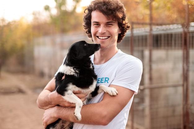 Gelukkige jonge kerel die als vrijwilliger in onderdak werkt en bastaardhond op handen draagt die bij camera glimlachen