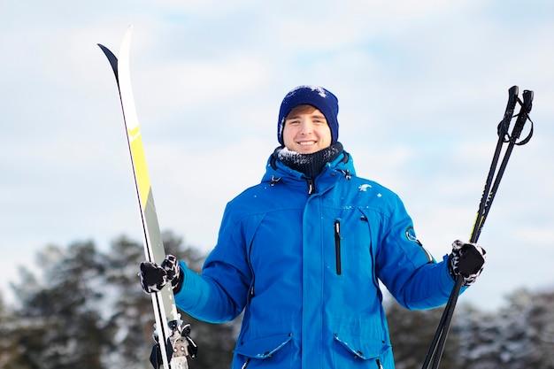 Gelukkige jonge kerel die ski's en stokken in het hele land in zijn handen houdt. de man leidt een gezonde levensstijl, een wintersport.