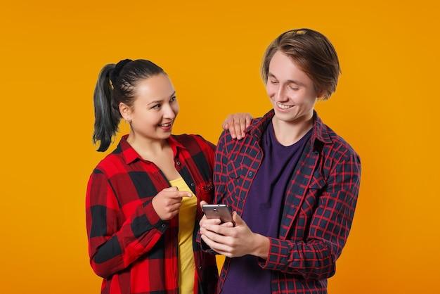 Gelukkige jonge kerel en meisje die naar het smartphonescherm kijken en glimlachen op een geeloranje