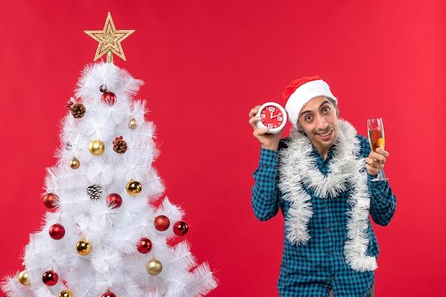 Gelukkige jonge kerel met de hoed van de kerstman en met een glas wijn en een klok die zich dichtbij kerstboom op rood bevinden