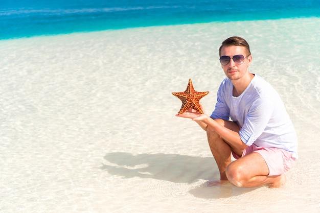 Gelukkige jonge kerel met zeester op wit strand binnen in het natuurreservaat