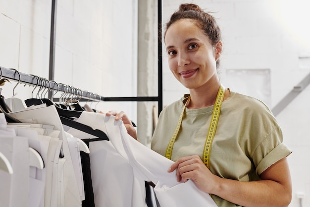 Gelukkige jonge kleermaker of creatieve modeontwerper met meetlint staan door rek met nieuw afgewerkte items en papieren patronen