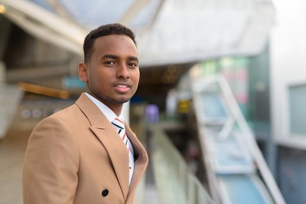 Gelukkige jonge knappe afrikaanse zakenman bij voetgangersbrug in de stad