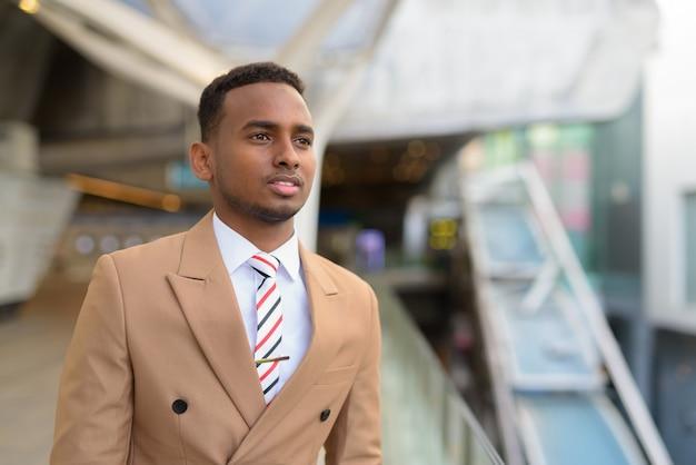 Gelukkige jonge knappe afrikaanse zakenman die bij voetgangersbrug in de stad denkt