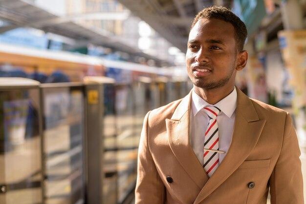 Gelukkige jonge knappe afrikaanse zakenman die en bij het hemelstation denken wachten
