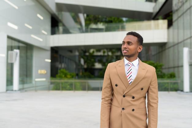 Gelukkige jonge knappe afrikaanse zakenman die in de stad denkt
