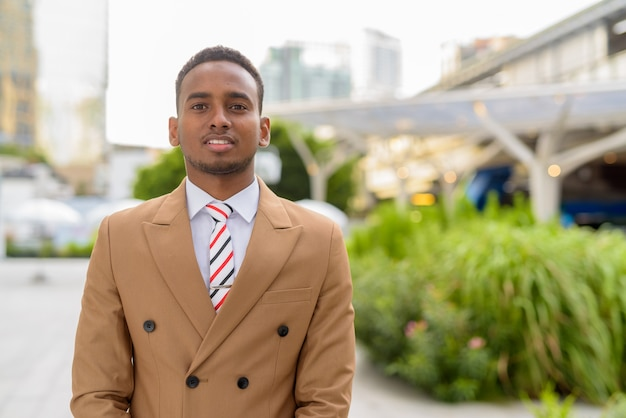 Gelukkige jonge knappe afrikaanse zakenman lachend in de stad buitenshuis