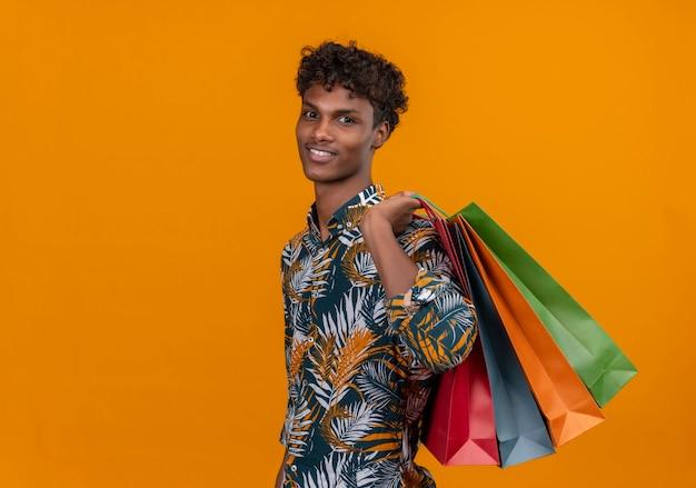 Gelukkige jonge knappe donkere man met krullend haar in bladeren bedrukt overhemd glimlachend boodschappentassen vasthoudend terwijl hij staat