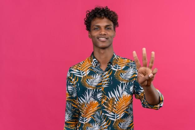 Gelukkige jonge knappe donkere man met krullend haar in bladeren bedrukt overhemd met vingers nummer drie