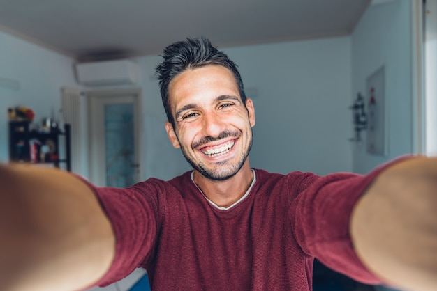 Gelukkige jonge knappe duizendjarige die een selfie neemt die in de huiskamer glimlacht.