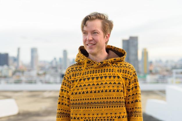 Gelukkige jonge knappe mens die met hoodie tegen mening van de stad denken