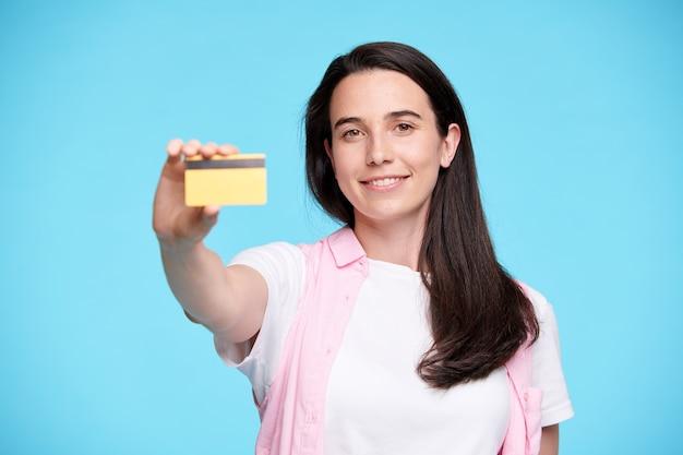 Gelukkige jonge koper of shopaholic die je plastic creditcard laat zien terwijl je geïsoleerd staat