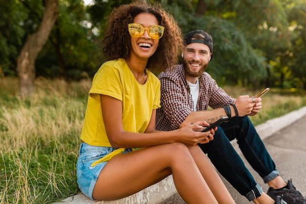 Gelukkige jonge lachende vrienden zitten park met behulp van smartphones, man en vrouw samen plezier