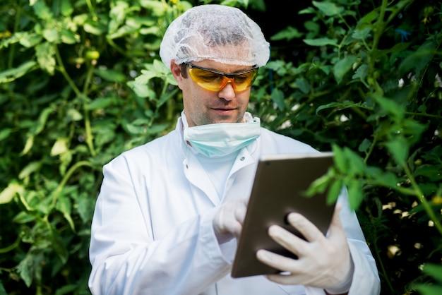 Gelukkige jonge landbouwer die een tablet in de serre bekijkt.