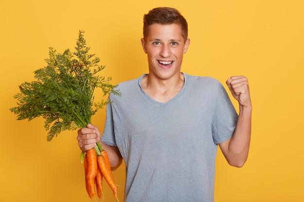 Gelukkige jonge landbouwer die zijn oogst van wortelen toont