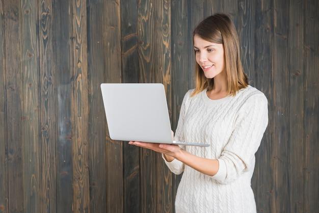 Gelukkige jonge laptop van de vrouwenholding tegen houten achtergrond