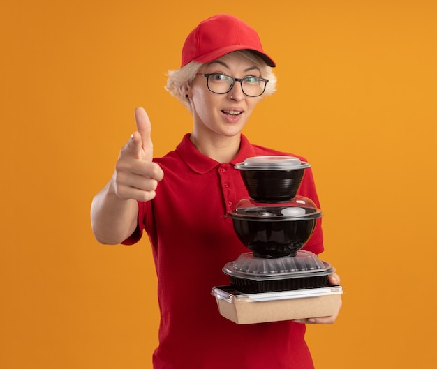 Gelukkige jonge leveringsvrouw in rood uniform en glb die glazen dragen die stapel voedselpakketten houden die met wijsvinger richten die zich zelfverzekerd over oranje muur glimlachen