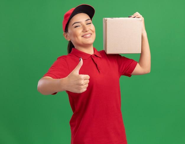 Gelukkige jonge leveringsvrouw in rood uniform en glb die kartondoos houden die voorzijde glimlachen die vrolijk tonen die omhoog duimen tonen die zich over groene muur bevinden