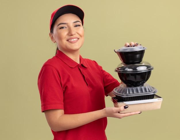Gelukkige jonge leveringsvrouw in rood uniform en glb-holdingsstapel voedselpakketten die voorzijde glimlachend vrolijk statusend over groene muur bekijken kijken